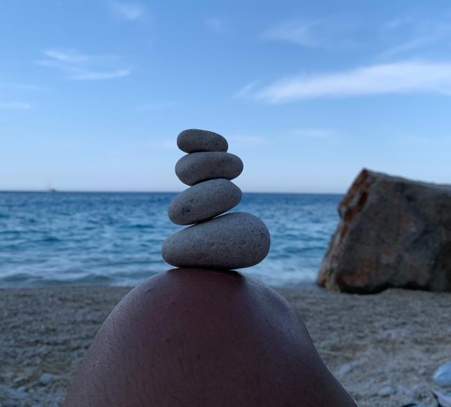 pedras de diferentes tamanhos em equilíbrio sobre um joelho. Vê-se o mar azul ao fundo.