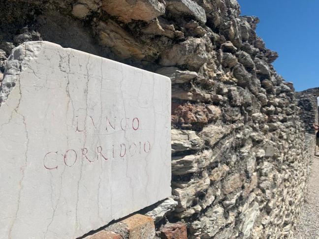 ruínas romanas com placa escrita lungo corridoio